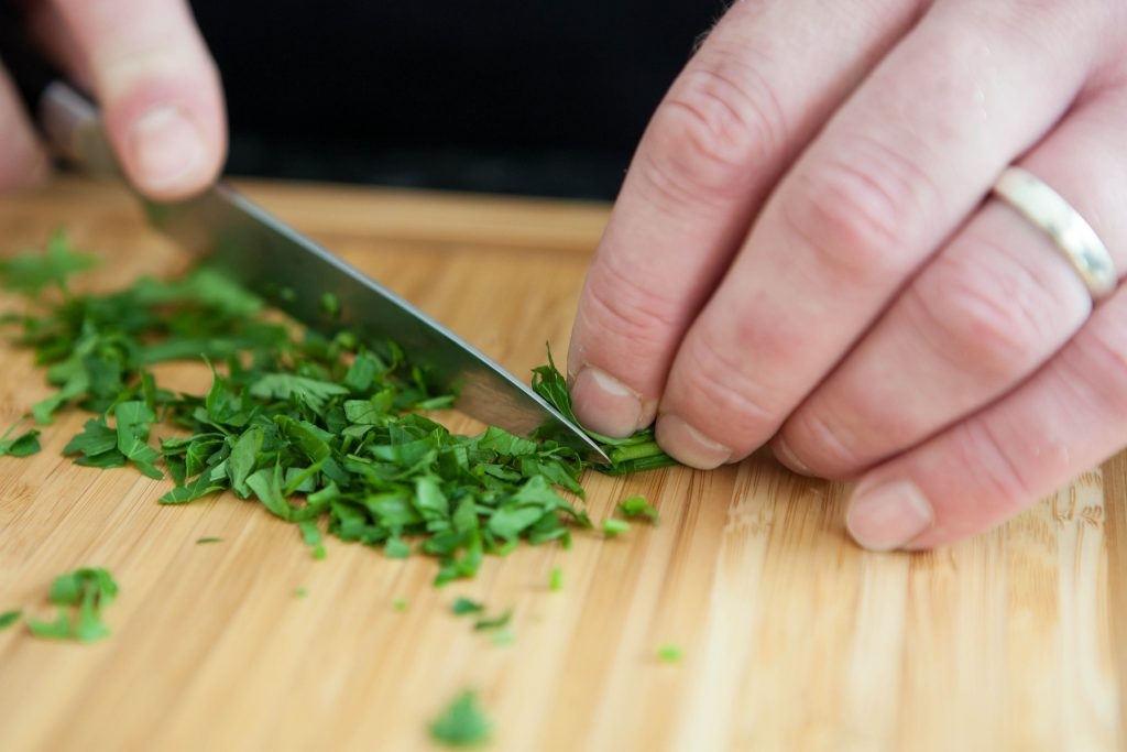 Hands holding a knife while cutting parsley