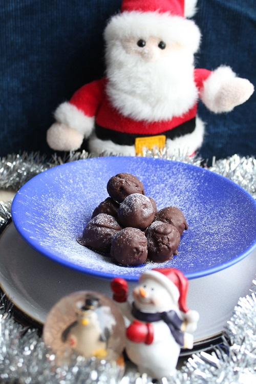 christmas pudding truffles on a platter with christmas ornaments around it