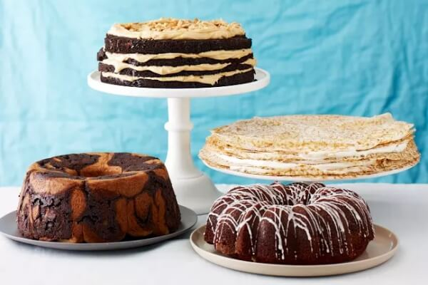 different types of cakes on platters of different sizes and heights