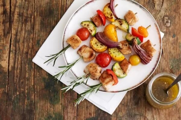 chicken and veggie skewers on platter seen from above