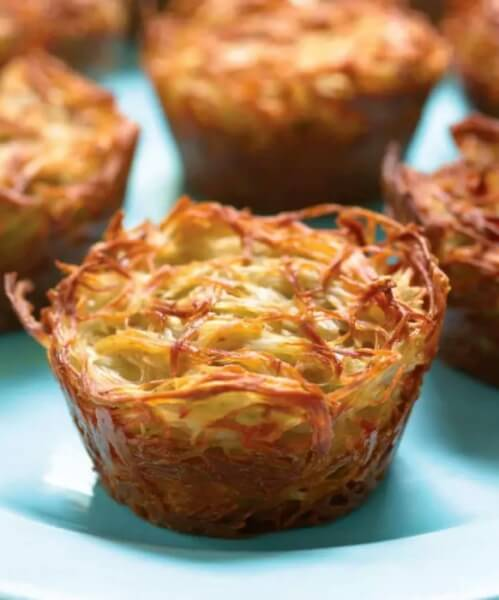 close up on potato kugel cup with blured cups in the background