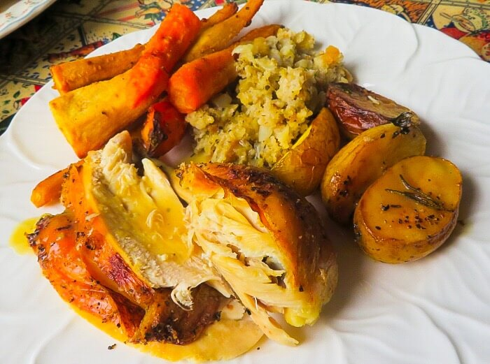 roast chicken on plate with vegetables and potatoes